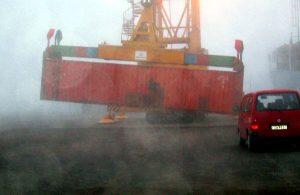 Containerverladung mit Autikran bei Nebel